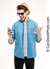 Close-up portrait of angry man shouting at his smartphone -...