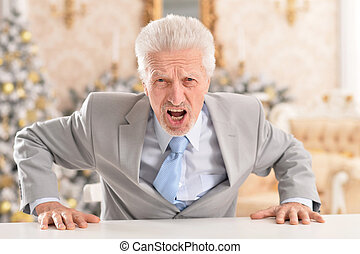 Close up portrait of angry senior businessman sitting at table