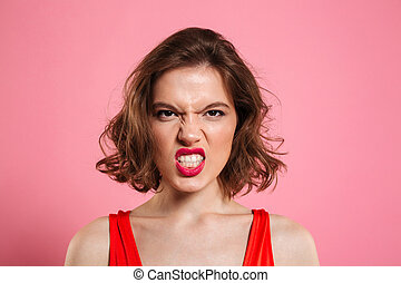 Close-up portrait of angry young woman with red lips looking...