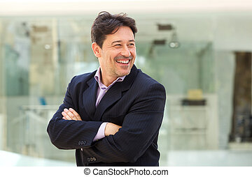 attractive businessman smiling in suit and looking away