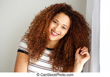 attractive mixed race woman with curly hair smiling