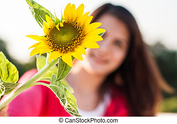 Close-up portrait of attractive woman with sunflowers in her hand