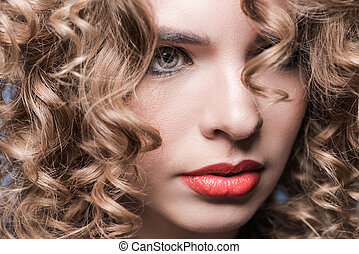 Close-up portrait of attractive young woman with curly hair looking away