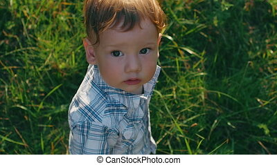 close up portrait of baby boy looks at camera on green grass background