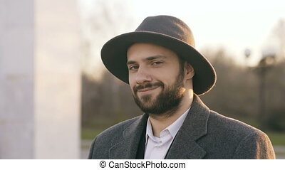Close up portrait of bearded young hipster businessman smiling and looking into camera at sunset on the street