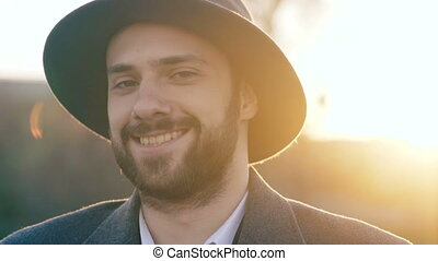 Close up portrait of bearded young hipster businessman smiling and looking into camera in street outdoors