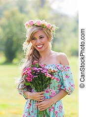 Close-up portrait of beautiful blonde girl holding bouquet ...