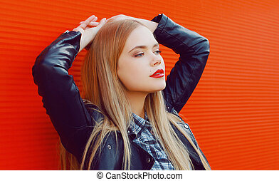 Close up portrait of beautiful blonde young woman on a red wall background