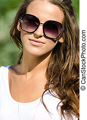 close up portrait of beautiful brunette fashion girl young woman in sunglasses white shirt smiling & looking at camera on green sunny summer outdoor background