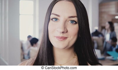 Close-up portrait of beautiful European female business woman with long straight hair, blue eyes in trendy office 4K.