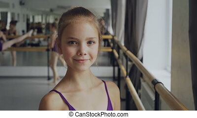 Close-up portrait of beautiful little girl in bodysuit standing in ballet class, smiling and looking at camera. Other students are doing exercises in background.