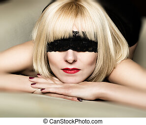 Close up portrait of beautiful sexy young blonde woman with a bandage on his eyes, put her head in the palm of your hand