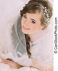 Close-up portrait of beautiful smiling bride with shining decoration in long curly hair