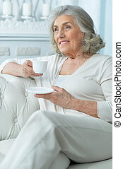 Close up portrait of beautiful smiling senior woman drinking tea