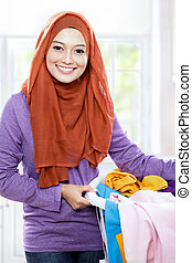 close up portrait of beautiful smiling woman wearing hijab holding a laundry basket