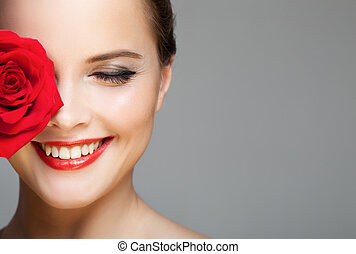 Close-up portrait of beautiful smiling woman with red rose. Make