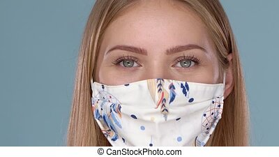 Close up portrait of beautiful woman wearing stylish face mask. Protection against viruses pollution