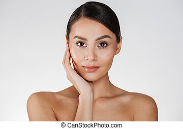 Close up portrait of beautiful woman with natural makeup posing at camera with touching her pretty face, isolated over white background