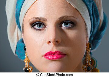 Close up portrait of beautiful woman with blue eyes with turban, studio shoot