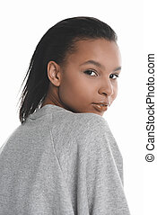 Close-up portrait of beautiful young african american woman in grey sweater looking at camera