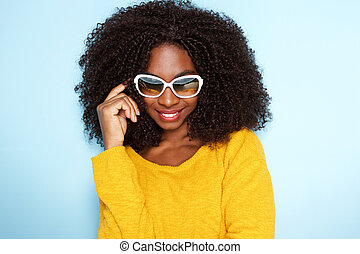 beautiful young african woman in stylish sunglasses on blue background
