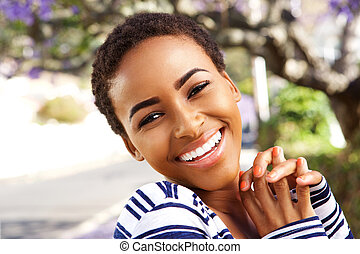 beautiful young black woman smiling outside in spring