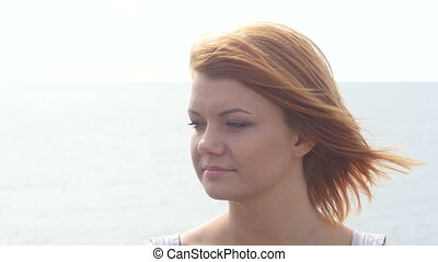 Close up portrait of beautiful young redhead woman on the beach