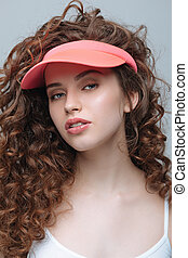 Close-up portrait of beautiful young hipster woman in pink cap looking at camera