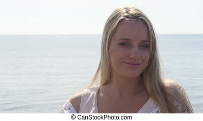 Close up portrait of beautiful young blond woman on the beach