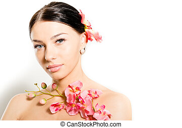 close up portrait of beautiful young woman bare shoulders brunette sexy spa girl with orchid flower in her head & holding pink orchid in hands looking at camera isolated on white copy space background