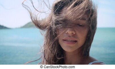 Close up portrait of beautiful young woman hair blowing in wind on the villa slow motion