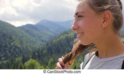 Close up portrait of beautiful young woman smiling in nature background of mountain