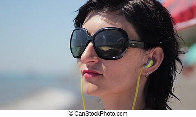 Close up portrait of beautiful young woman with headphones and sunglasses listening music on sea background