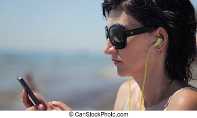 Close up portrait of beautiful young woman with headphones and sunglasses listening music on smartphone on sea background
