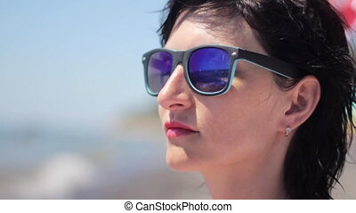 Close up portrait of beautiful young woman with sunglasses on tropical beach
