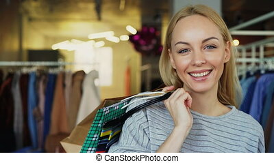 Close-up portrait of blond girl standing with paper bags in...