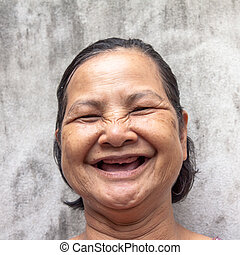 Close up portrait of broken tooth Thai woman laughing -...