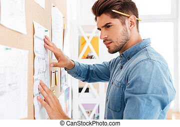 Close up portrait of businessman posting diagram at the board