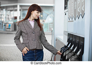 Close up portrait of charming young Caucasian business woman in trendy smart casual clothes, taking filling gun nozzle from gas station pump panel