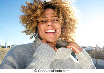 cheerful african american woman with curly hair laughing