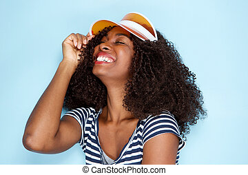 cheerful african woman wearing cap and smiling on blue background