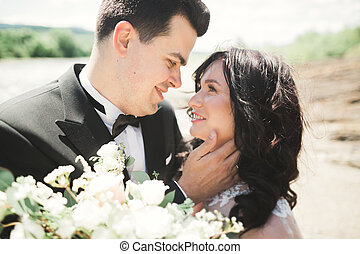 Close up portrait of couple against river and green trees. Beautiful young woman kissing handsome man outdoors