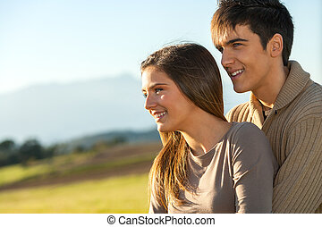 Close up portrait of couple outdoors at sunset.