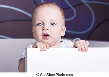 Close-up portrait of cute baby boy in a crib. Adorable open-mouthed baby boy looking at camera