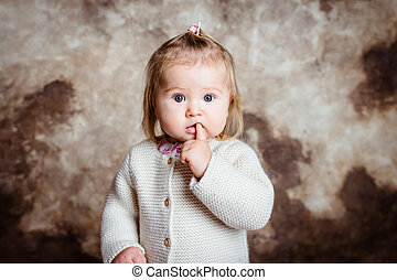 Close-up portrait of cute blond little girl with big grey eyes