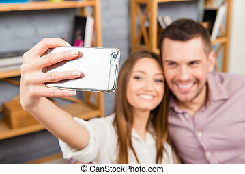 Close up portrait of cute couple making photo on smartphone