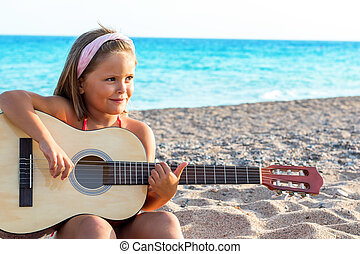 Close up portrait of Cute little girl with headband playing guitar on beach.