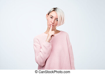 Close up portrait of cute lovely attractive woman with stylish hairdo making shhh or hush gesture