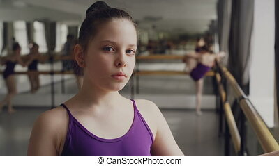 Close-up portrait of dark-haired little girl in bodysuit standing in ballet class and looking at camera. Other students are practising in background.