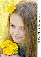 Close-up portrait of eight-year-old girl with dandelions in hands